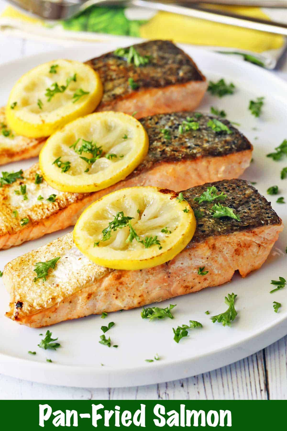 Three pan-fried salmon fillets topped with lemon slices and parsley.