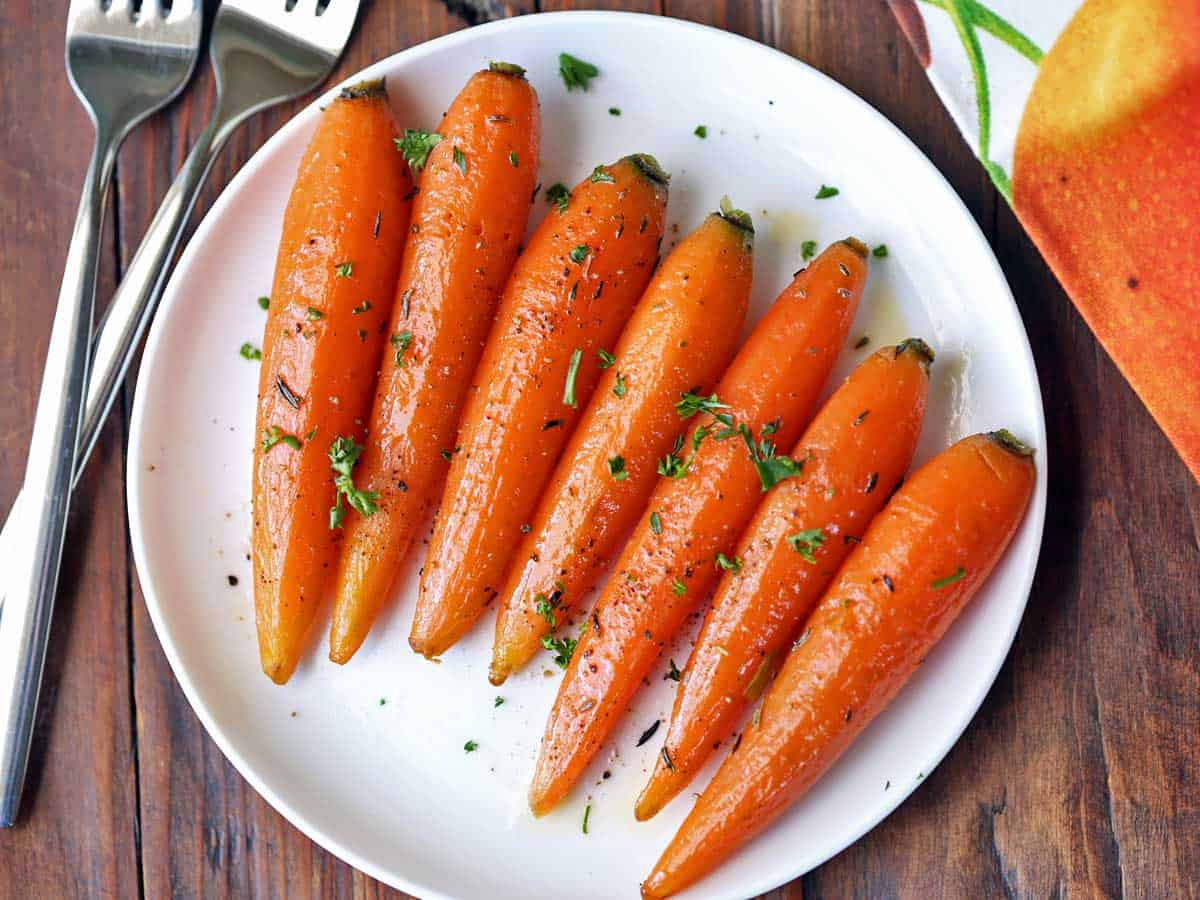 Petite glazed carrots served on a white plate.
