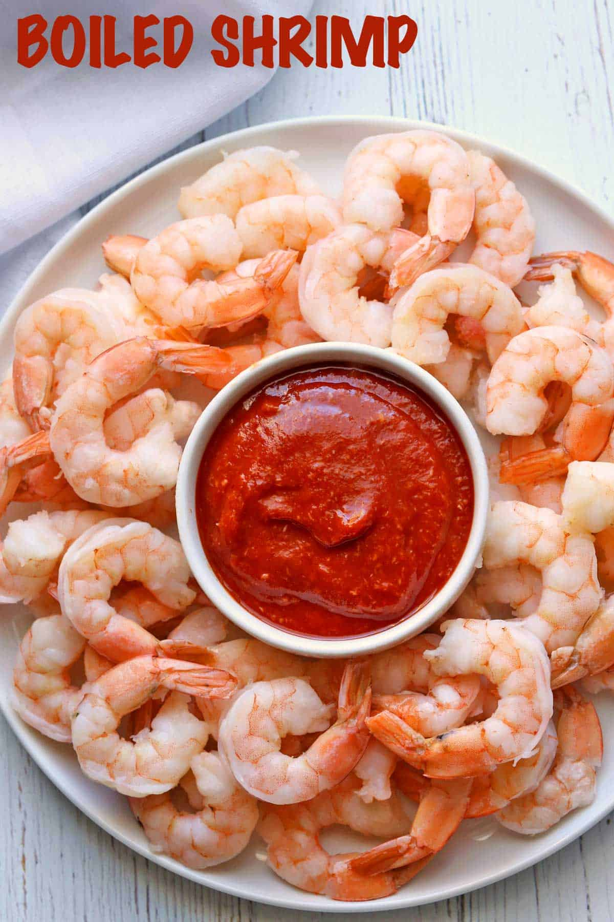 Boiled shrimp served with cocktail sauce.