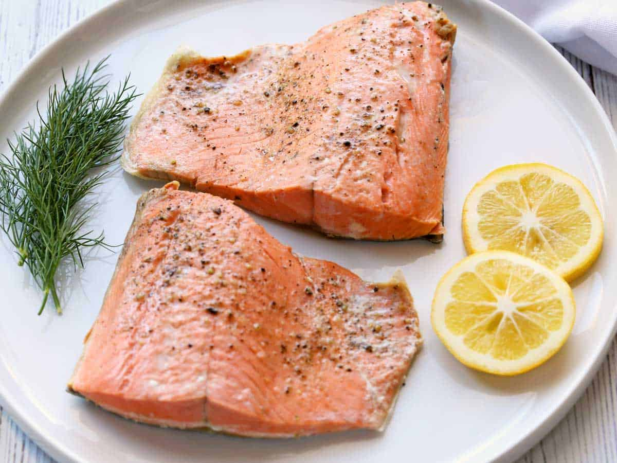 Two poached salmon fillets served on a white plate, garnished with dill and lemon slices.