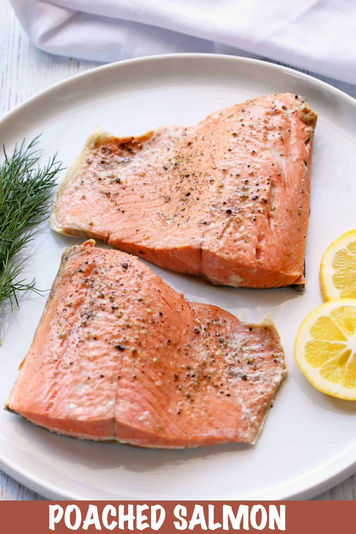 Poached salmon served with lemon slices and dill.
