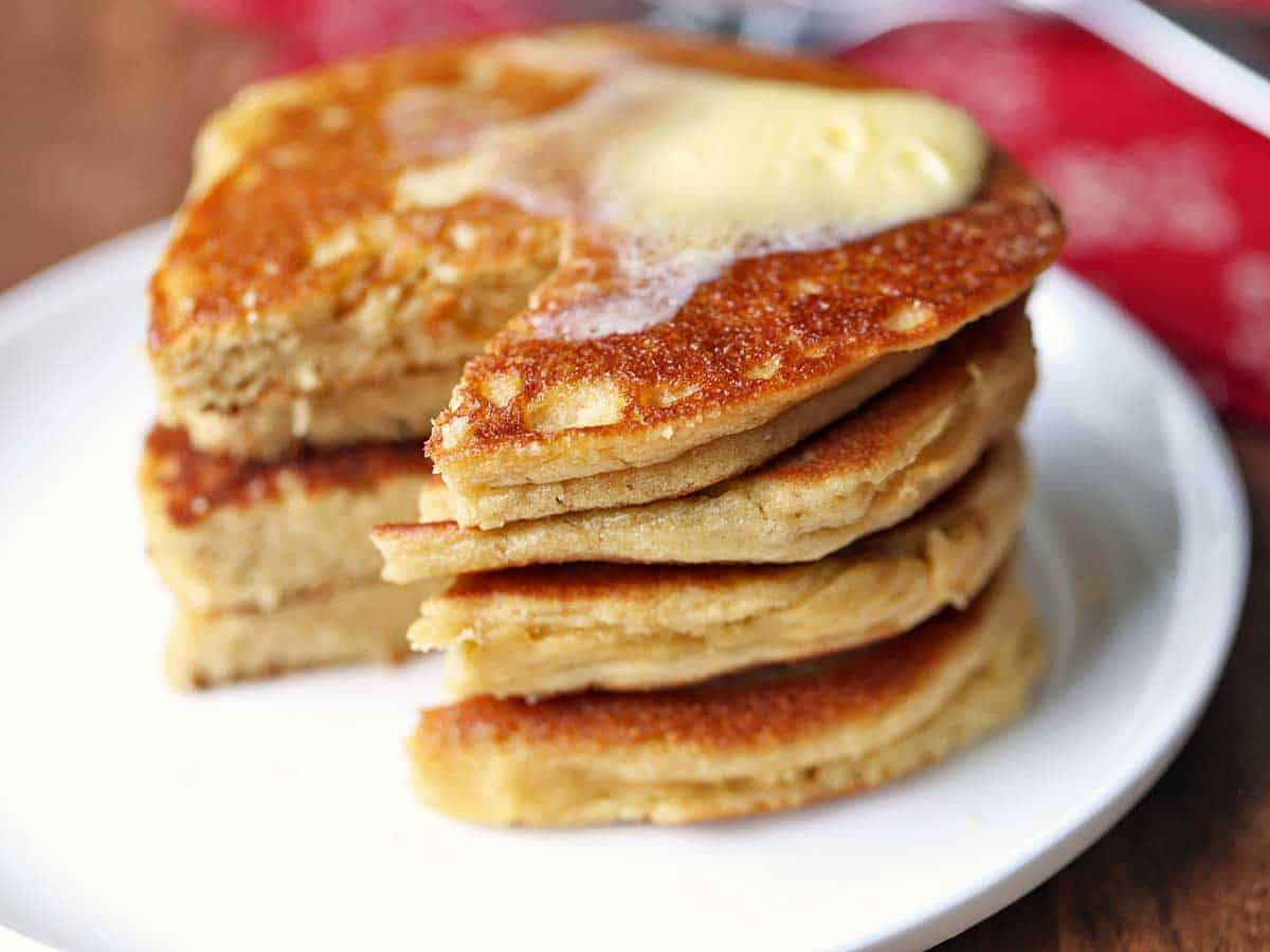 A stack of almond flour pancakes topped with butter