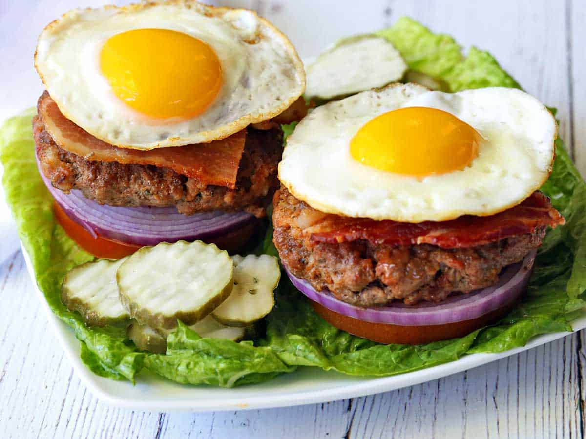 Two bacon burgers topped with fried eggs