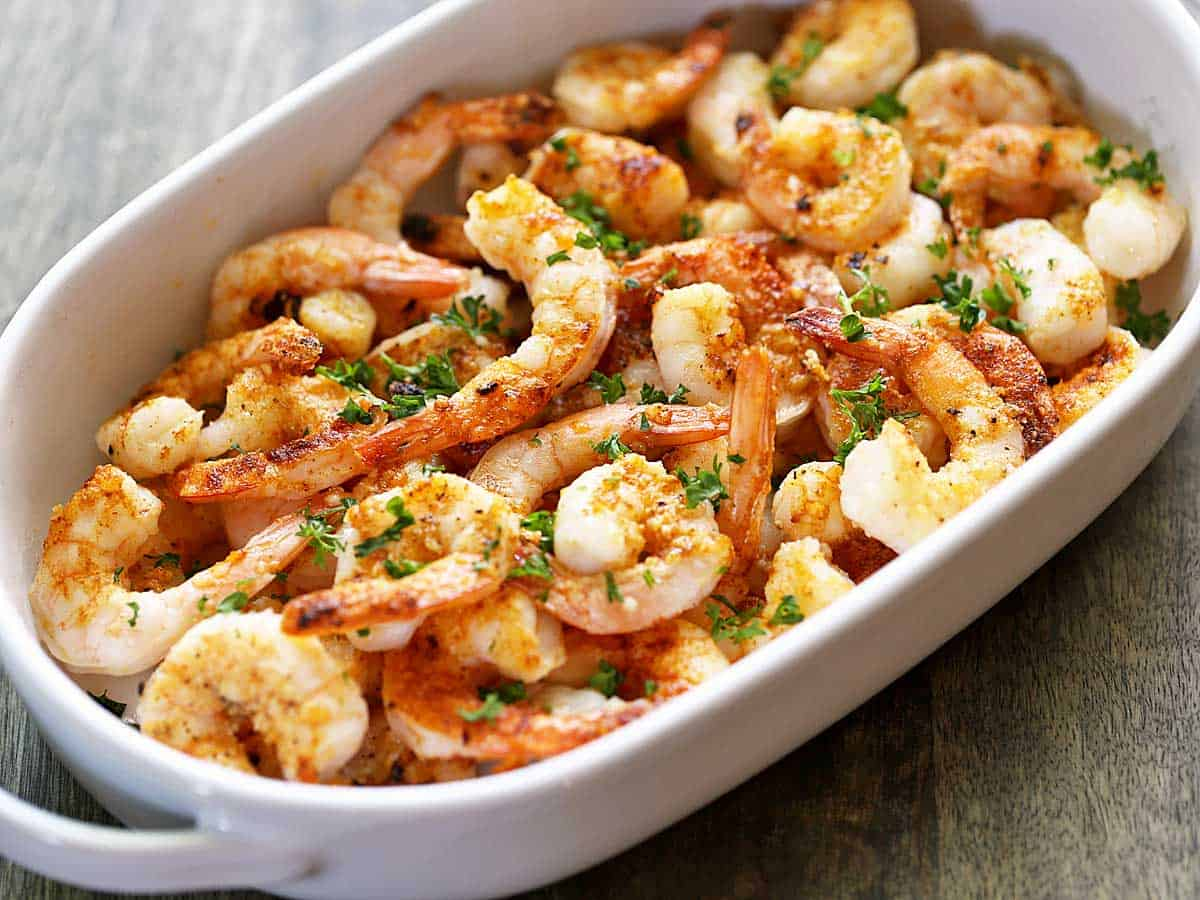 Baked shrimp served in a white dish and topped with parsley.