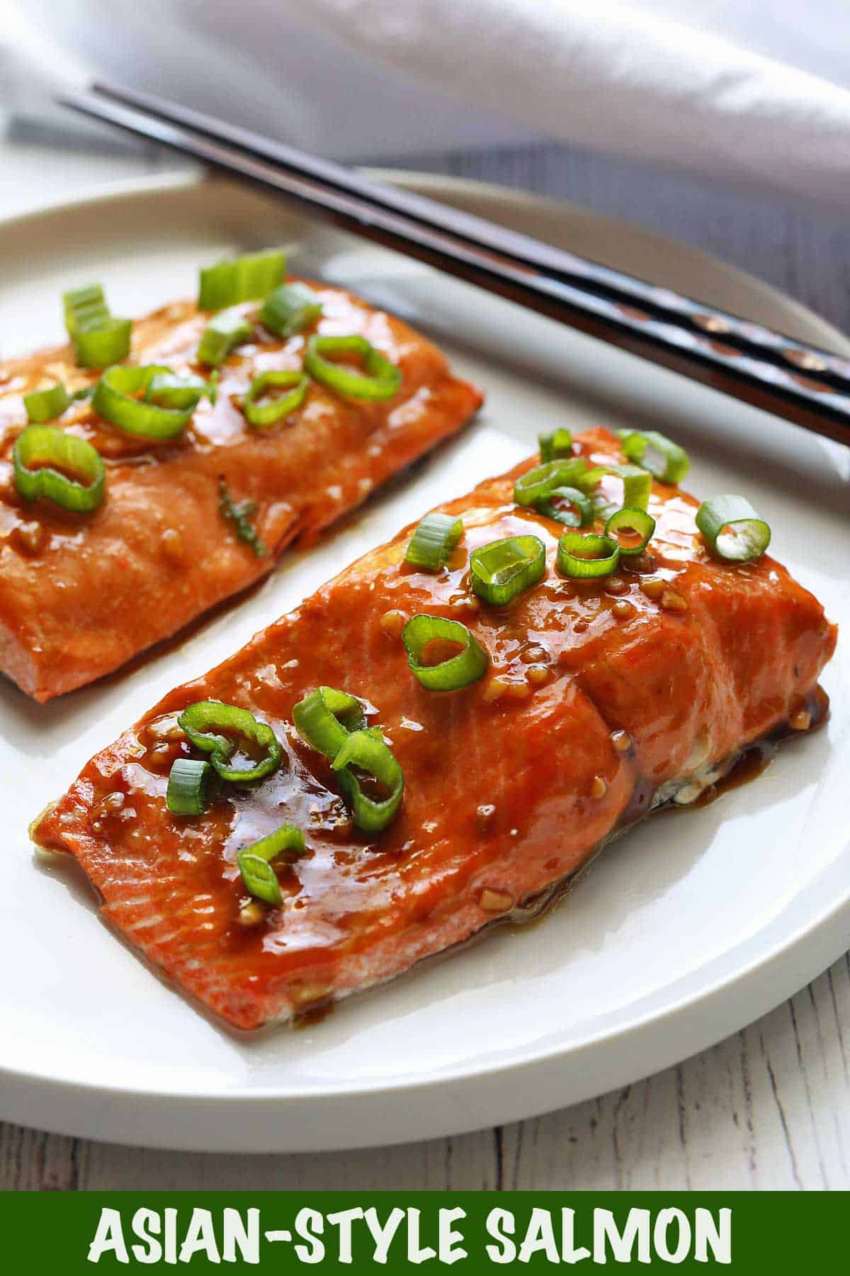 Salmon coated in Asian-style glazes served on a white plate with chopsticks.