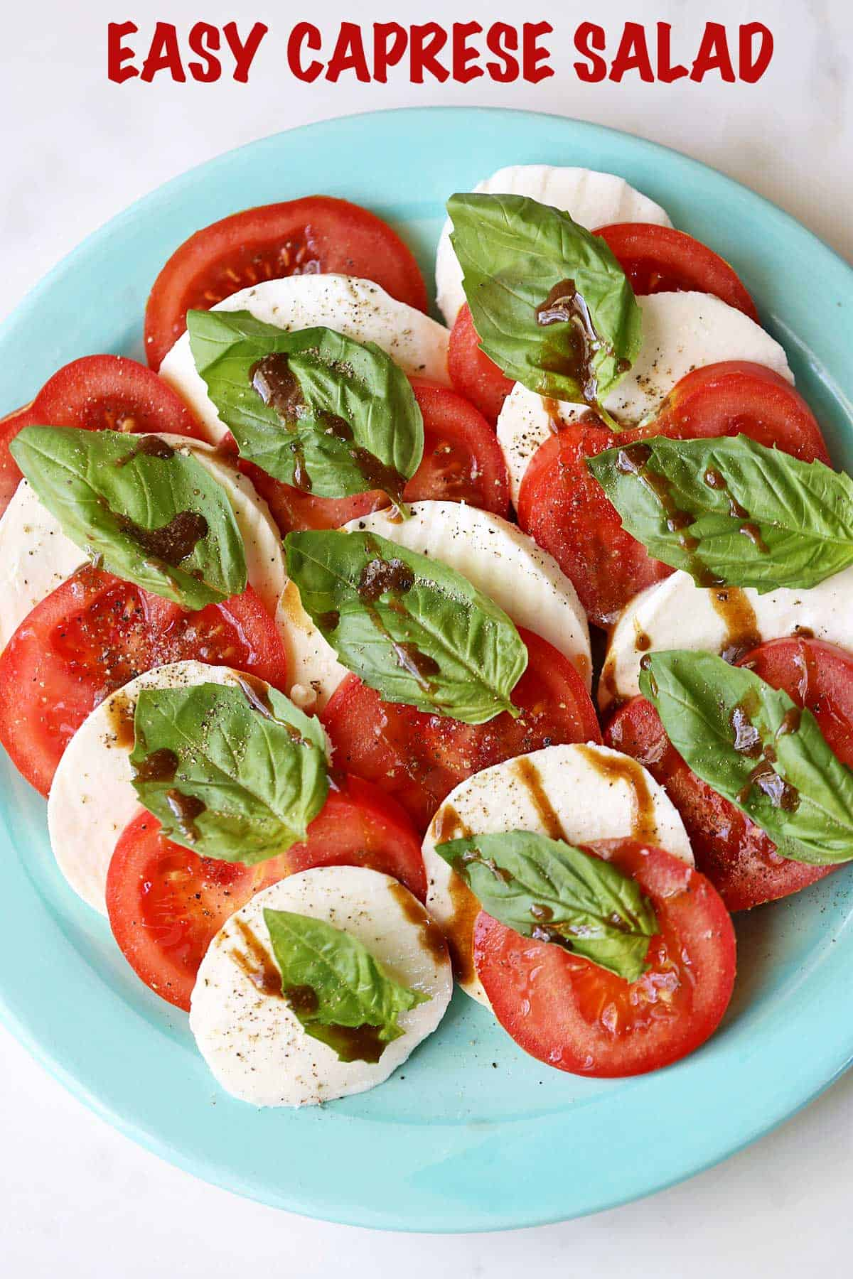Caprese salad with slices of tomatoes and mozzarella served on a green plate.