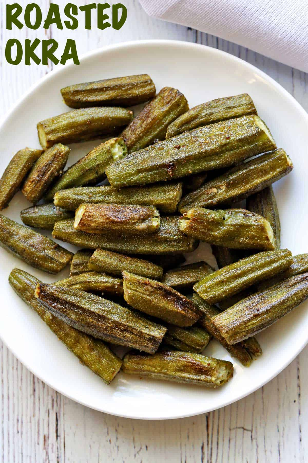 Roasted okra served on a white plate with a white napkin.