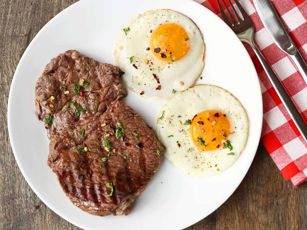 Steak and two fried eggs served on a white plate with a checkered napkin and utensils.