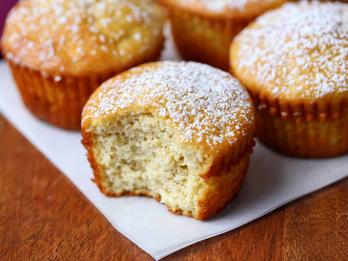 Four almond flour muffins dusted with powdered sugar.