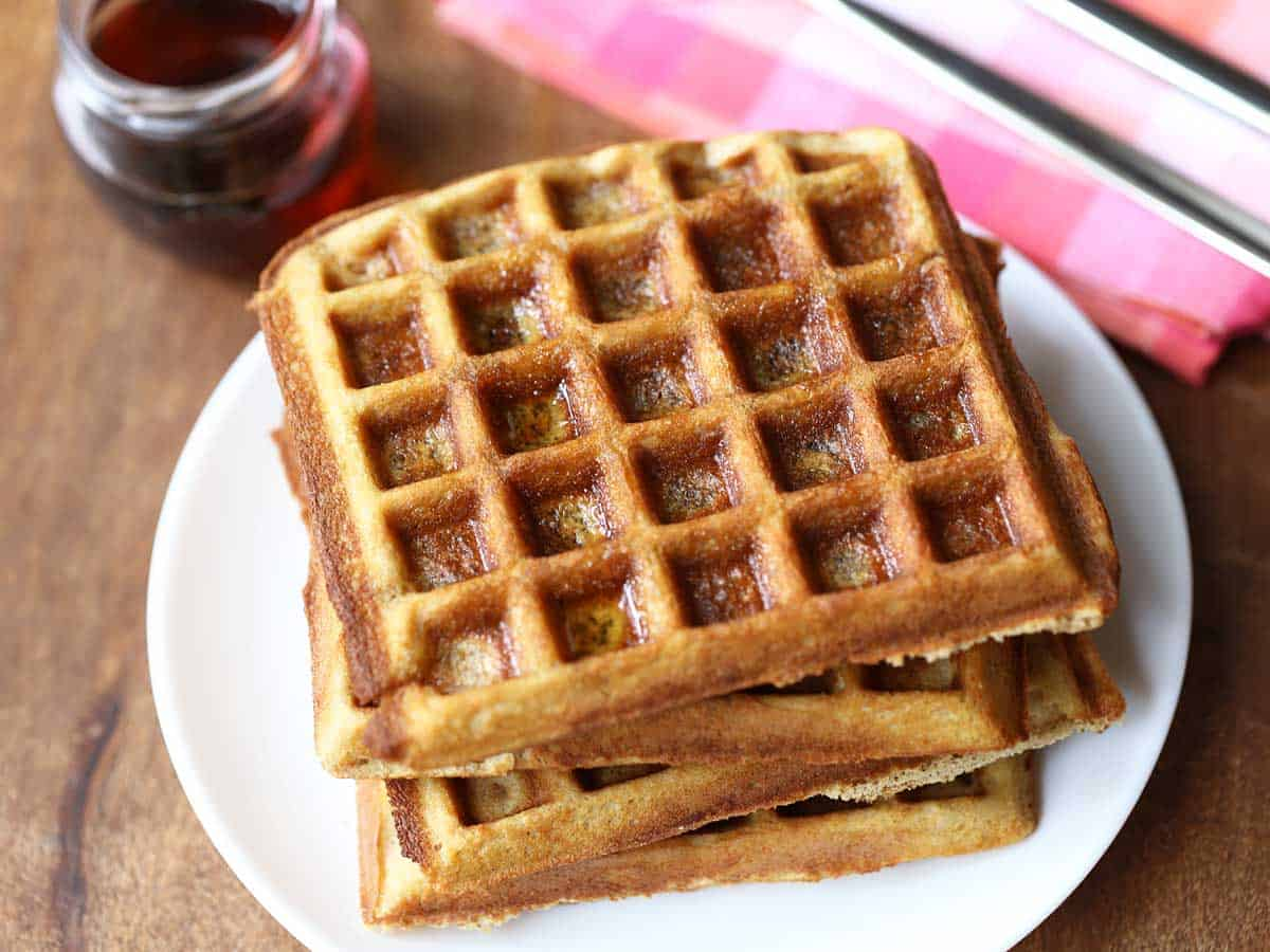 Keto almond flour waffles served with syrup and a checkered napkin.