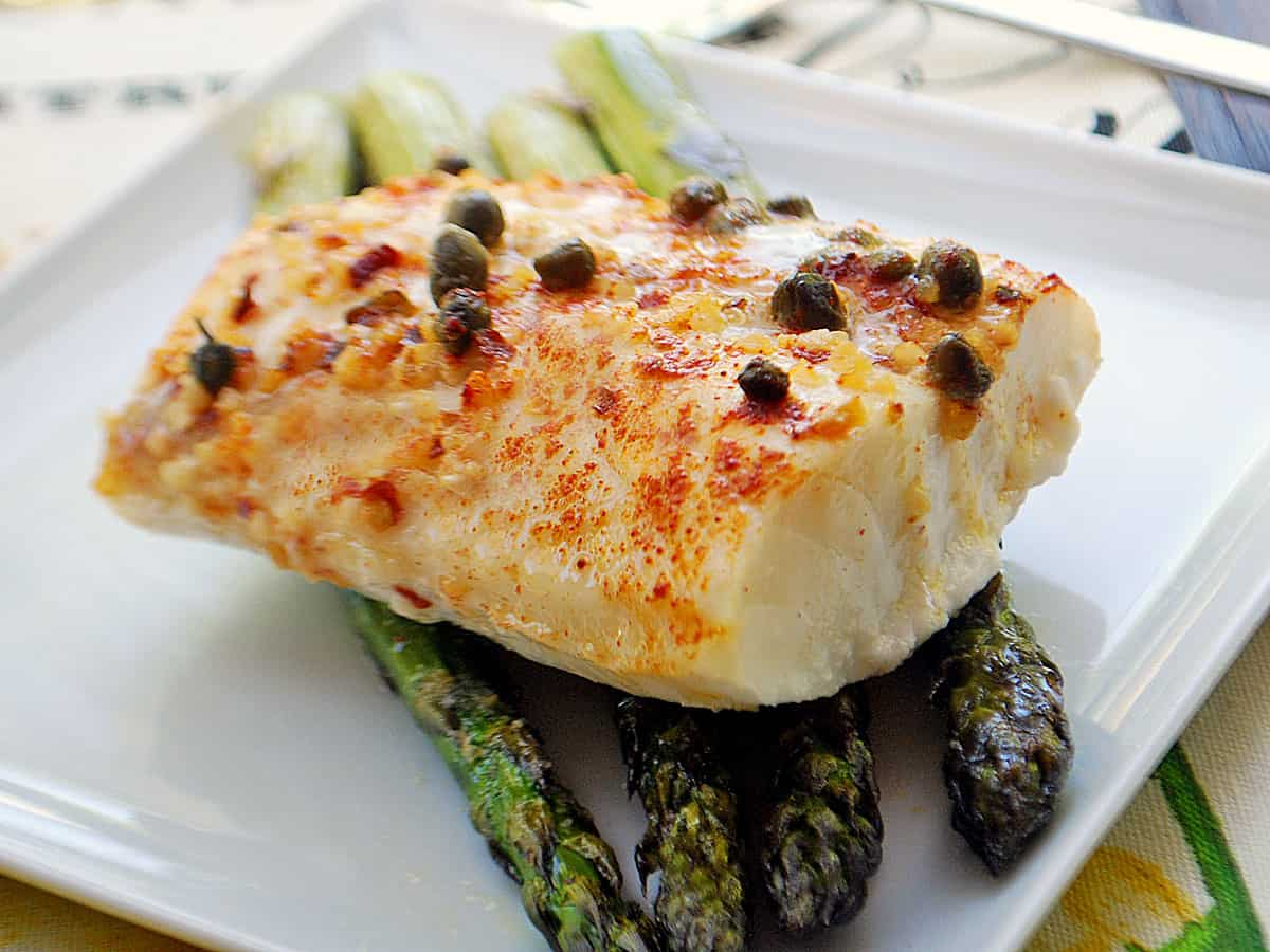 Baked cod fillet served on a bed of asparagus spears.
