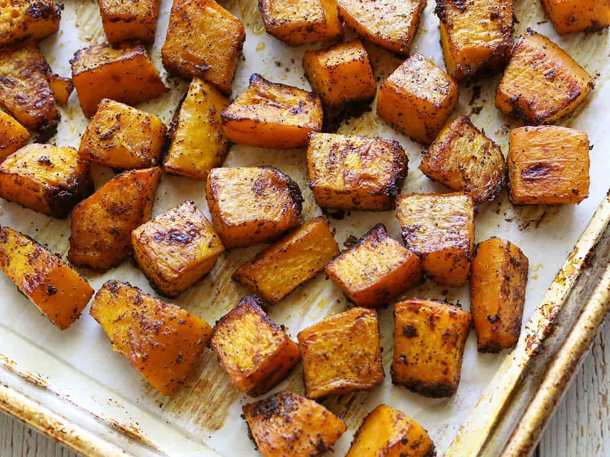 Baked pumpkin cubes spread on a roasting pan.