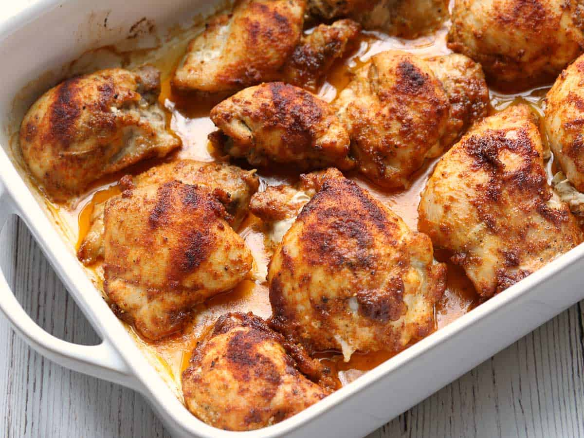 Boneless skinless chicken thighs served in a white baking dish.