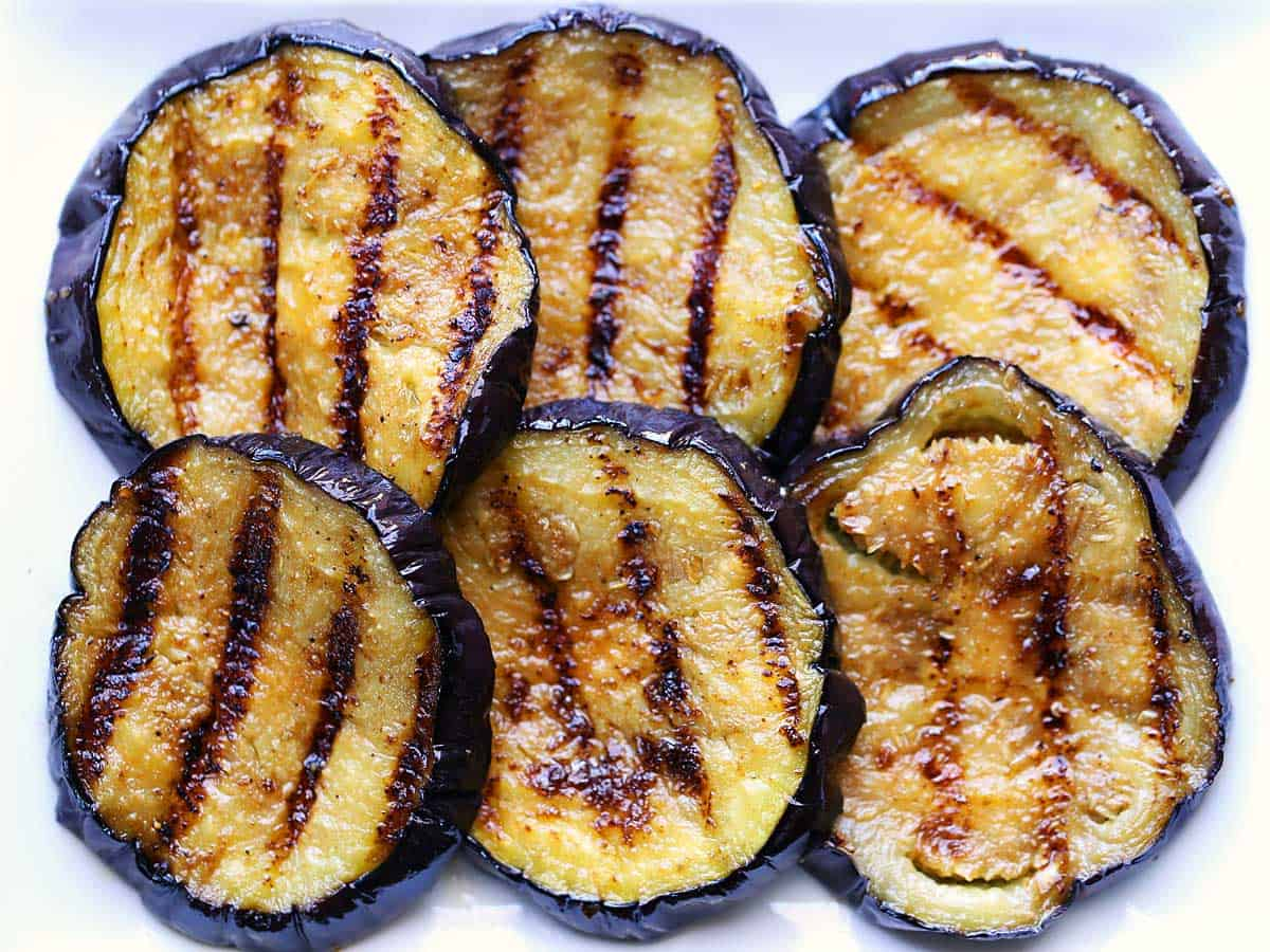 Slices of grilled eggplant arranged on a plate.