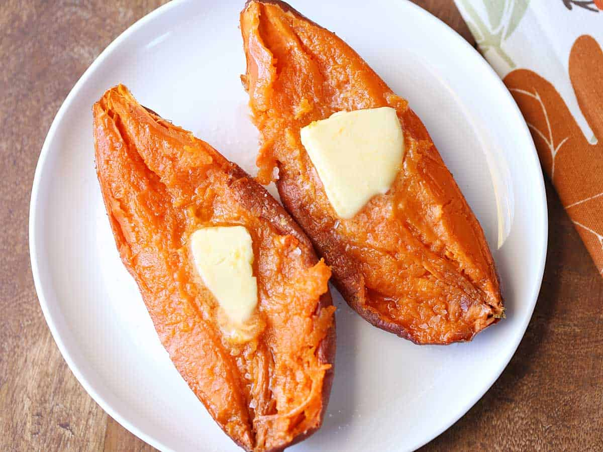 Two microwave sweet potato halves served on a white plate and topped with butter.