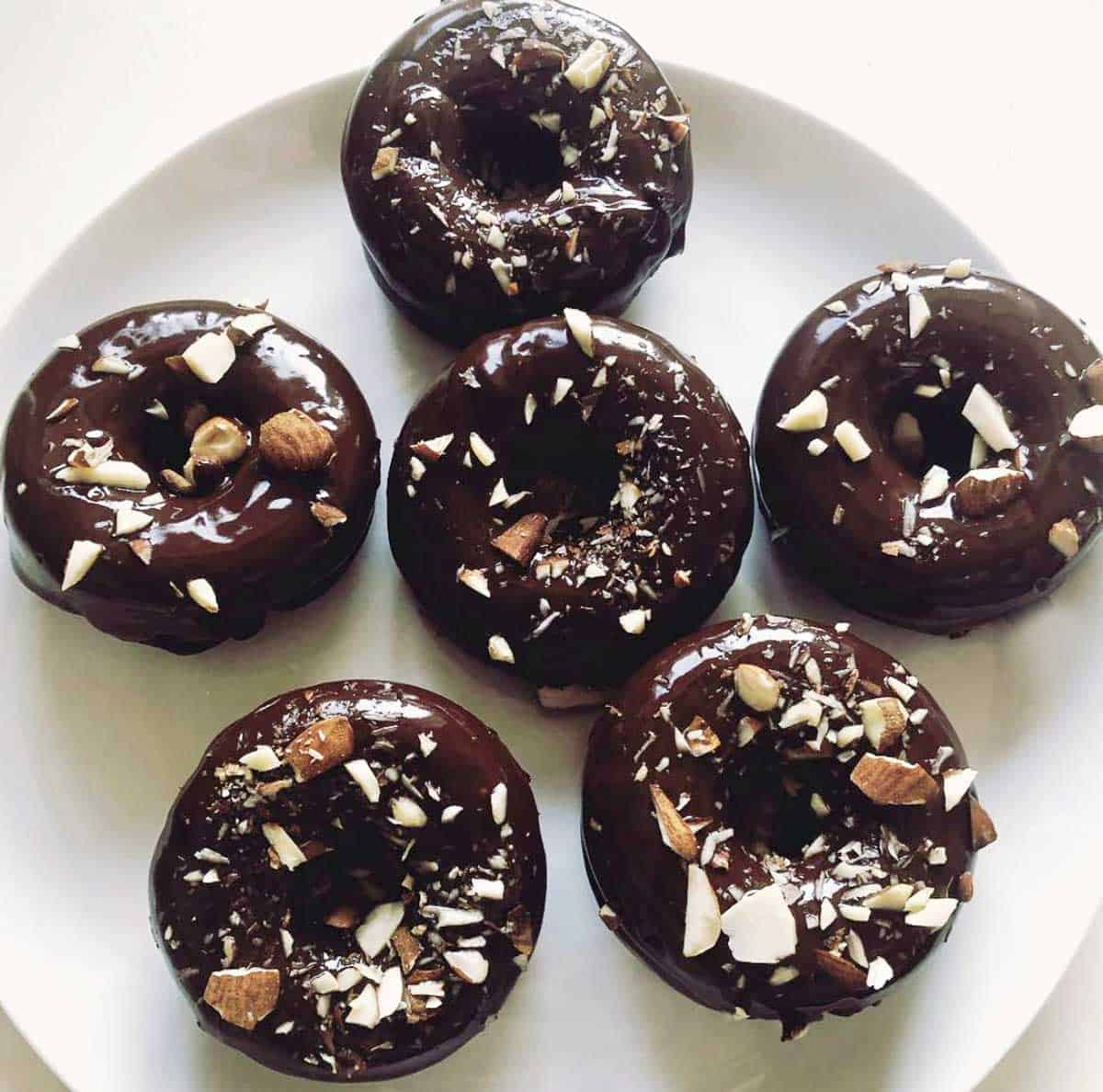 Low-carb chocolate donuts topped with chopped nuts.