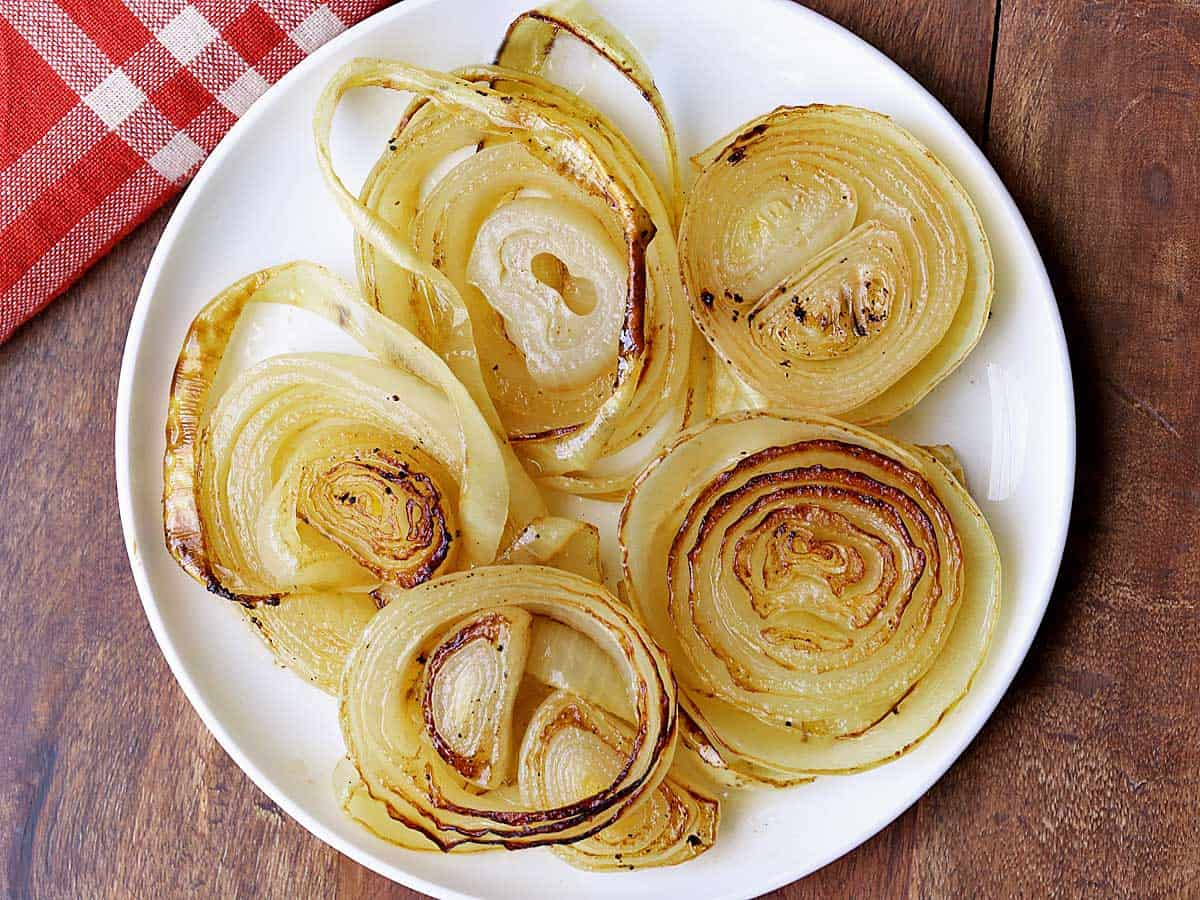 Roasted onions served on a white plate with a red napkin.