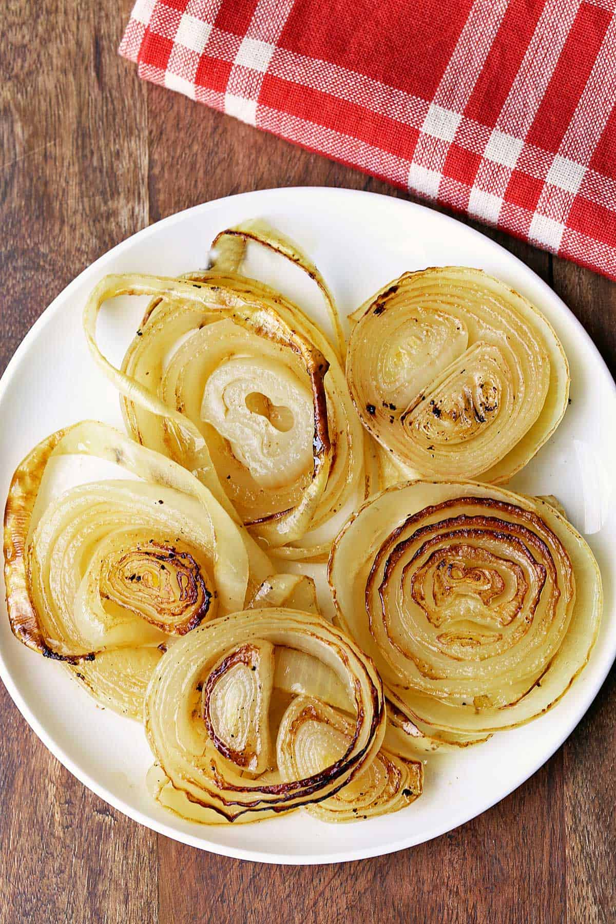 Baked onions served on a white plate with a red napkin.