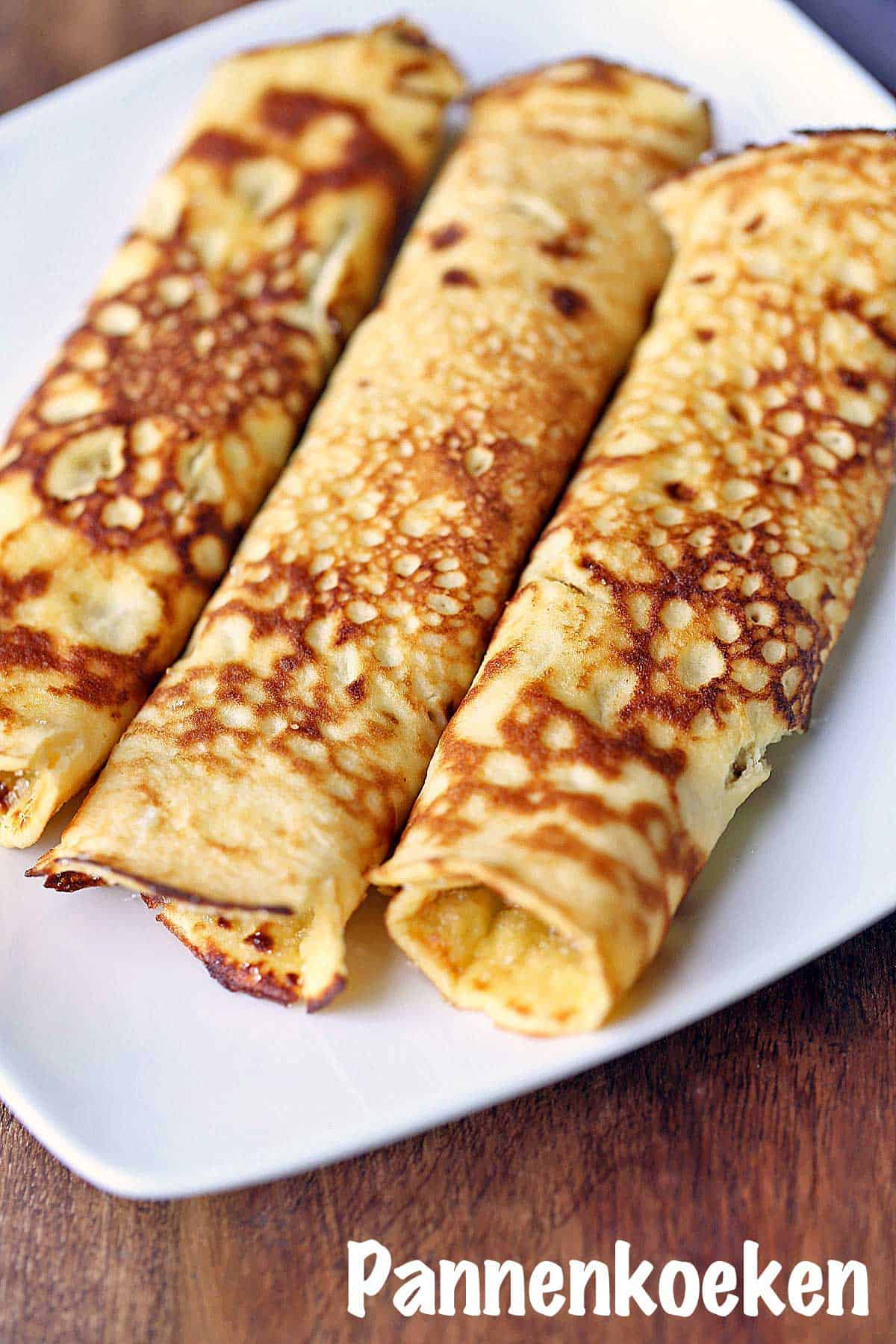 Three pannenkoeken rolled up and served on a white plate.