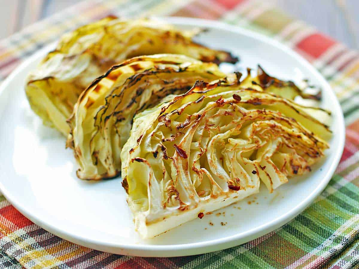 Roasted cabbage wedges served on a white plate.