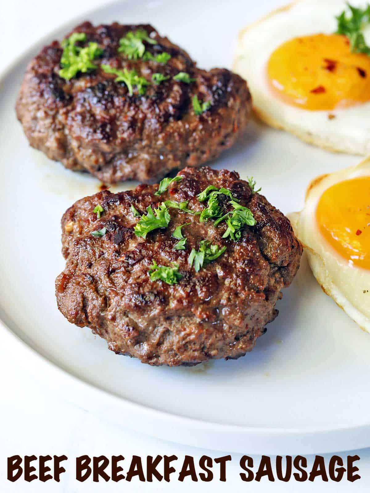Two beef sausage patties served with fried eggs.