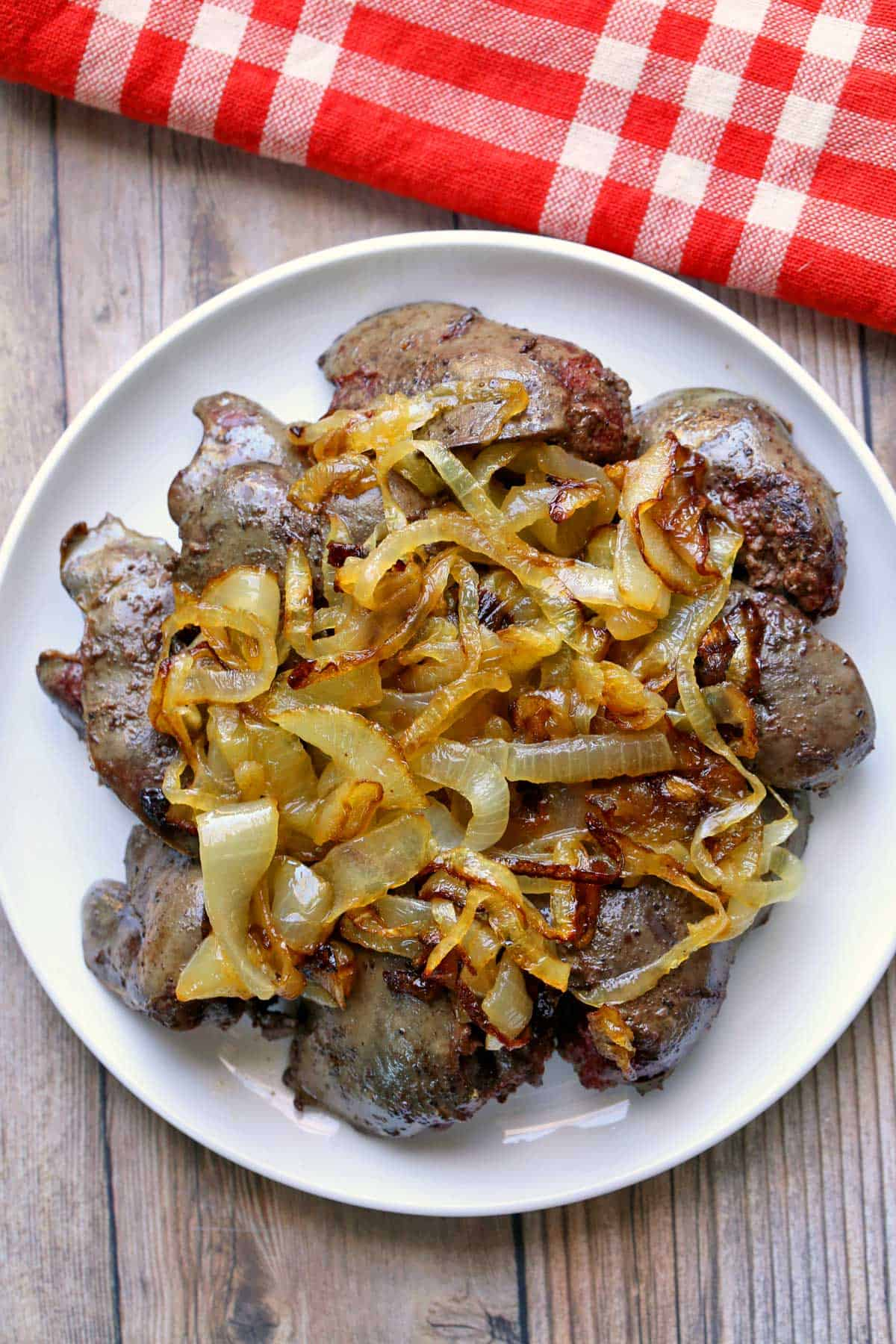 Pan-fried chicken livers topped with onions, served on a white plate.