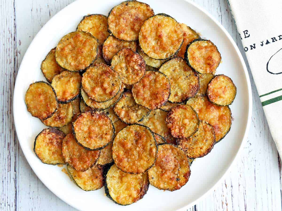 Zucchini chips served on a white plate with a napkin.