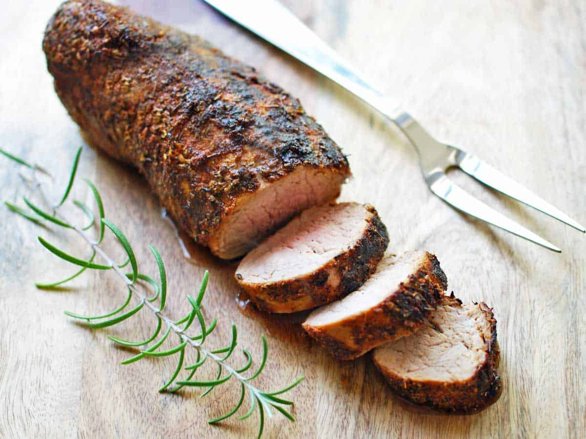 Oven roasted pork tenderloin, sliced and served on a cutting board.